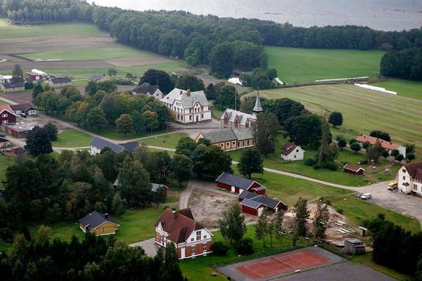 Vedere aeriană a închisorii Bastøy. În centru putem observa biblioteca și biserica. Pe insulă se află terenuri agricole, pădure și 80 de clădiri. Penitenciarul funcționează ca un sat care se autosusține economic.